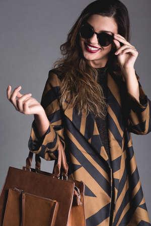 mujeres fashion: Mujer de la elegancia en traje marrón, que llevaba gafas, de pie sobre fondo gris