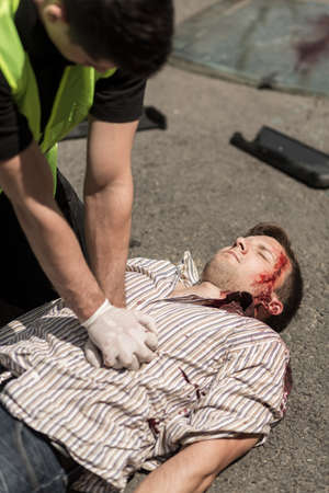 accident rate: Unconscious man lying on the street is being resuscitated Stock Photo