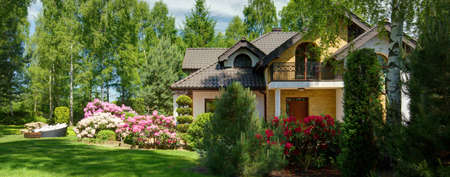 home and garden: Panoramic view of luxurious villa with secluded blooming garden Stock Photo