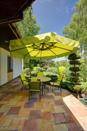 sunshade: Image of green garden furniture with sunshade umbrella on terrace