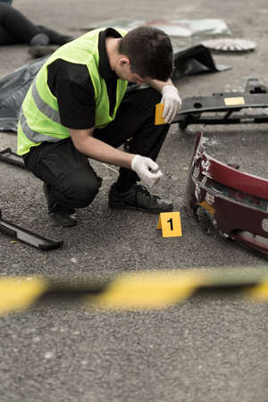 enquiring: Policeman is numbering evidences in car accident