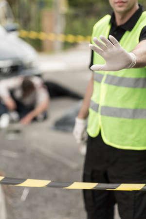 forbidding: Policeman is forbidding anyone to enter crash site