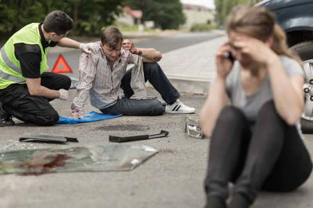 People sitting on the road after car crash Foto de archivo