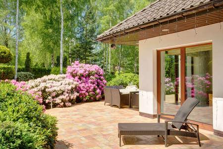 jardines con flores: Foto del espacio de relax con tumbonas junto a la casa de lujo Foto de archivo
