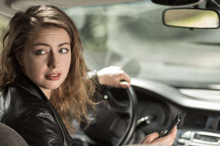driving a car: Young woman is distracted while driving car