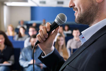 lecturer: Close up of lecturer with microphone, talking to group of students