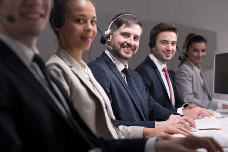 teleoperator: Group of smiling call center workers Stock Photo