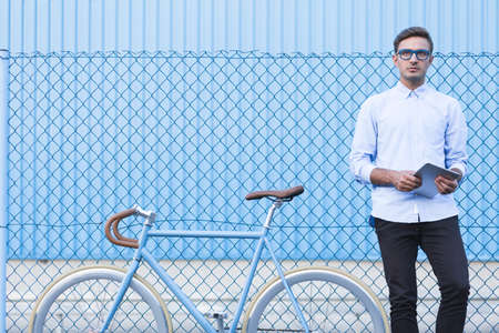 using tablet: Young businessman with bike leading active lifestyle Stock Photo