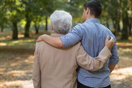 persona caminando: Abrazado nieto y abuelo en el parque