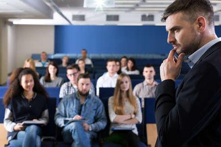 jovenes estudiantes: Hombre en el juego que da conferencia en la universidad para estudiantes jóvenes