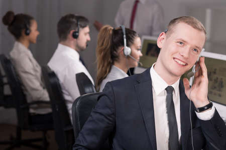 telephone salesman: Man in suit working in call center, smiling