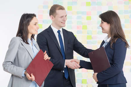 success business: Business partners shaking their hands in light interior
