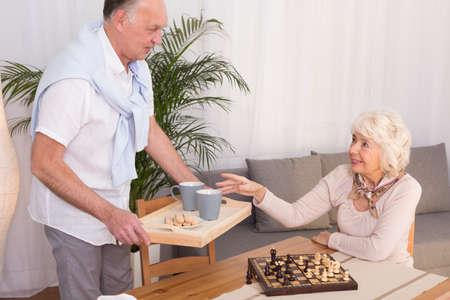 beside table: Senior woman sitting beside table with chess, elderly man serving tea
