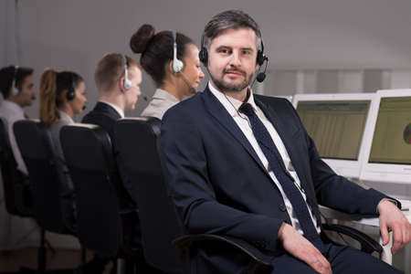 teleoperator: Man in suit with headset working in call center