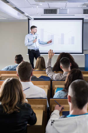 college professor: Young man giving speech in lecture hall for a group of students