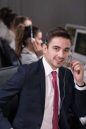 teleoperator: Young salesman in suit working in call center