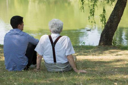 grandkid: Grandfather with grandchild sitting at the lake