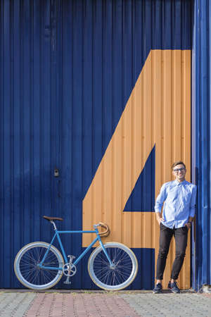 ecofriendly: Eco-friendly man with city bicycle leaning against garage