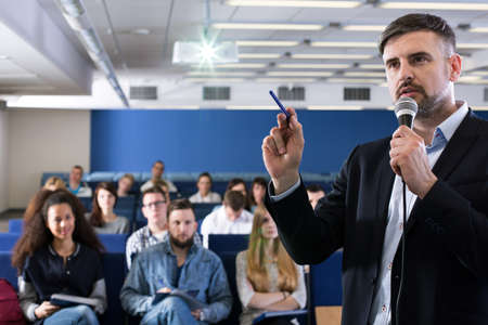 Academic teacher talking to his students in lecture hall Stock Photo