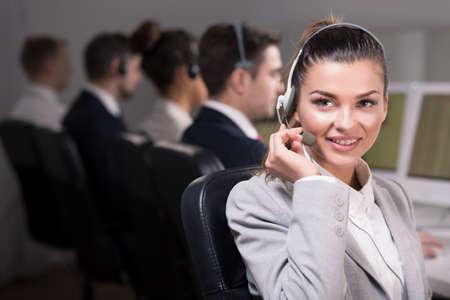 servicio al cliente: vendedora joven y hermosa con auriculares, sonriente Foto de archivo