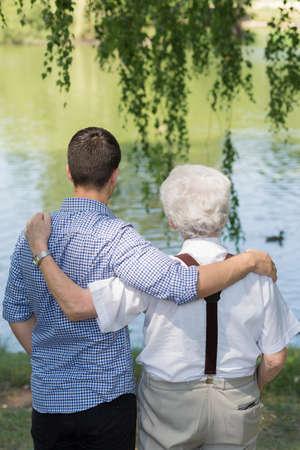 grandson: Grandpa and grandson standing at the lake