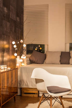 interior lighting: Warm interior with decorative lighting, white chair and bed