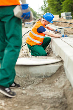 kerb: Busy workman installing kerb at construction site Stock Photo
