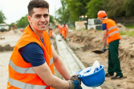 asphalt: Smiling building worker holding helmet in hand