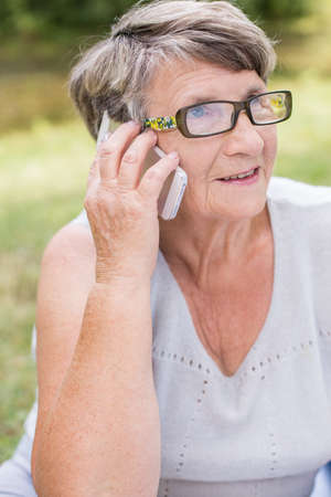 someone: Elder lady is calling to someone by phone Stock Photo