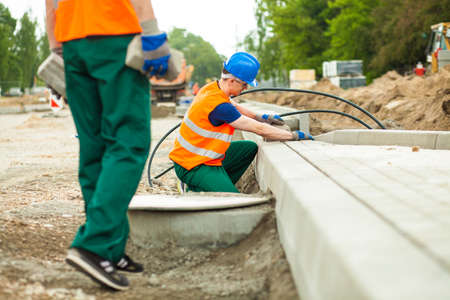 kerb: Young workmen installing kerb on the road