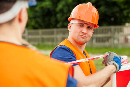 putting up: Smiling construction worker putting up warning road signs