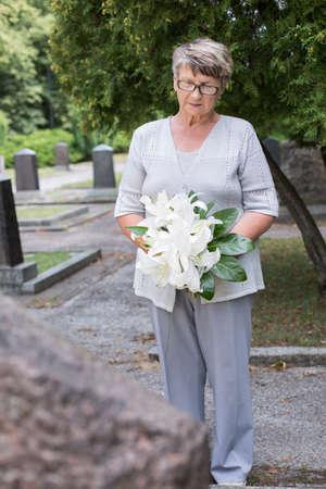 señora mayor está llevando a cabo una ofrenda floral