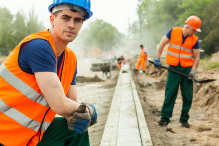 kerb: Young building worker on knees installing kerb on the road