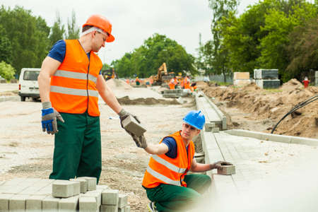 asphalt: Building worker giving paving stone to colleague Stock Photo