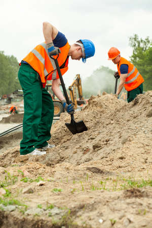 Construction worker using a spade to dig