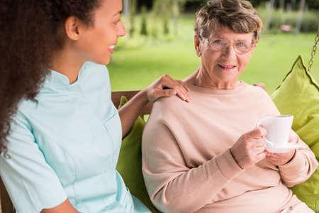 wrinkled: Elder lady is drinking tea in the garden Stock Photo