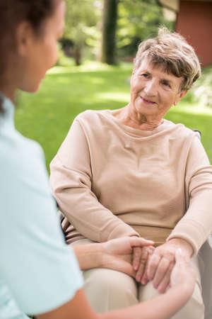 La enfermera está cuidando más vieja señora