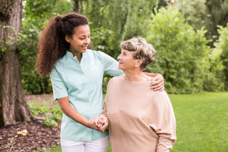 care at home: Nurse is walking around with elder lady Stock Photo