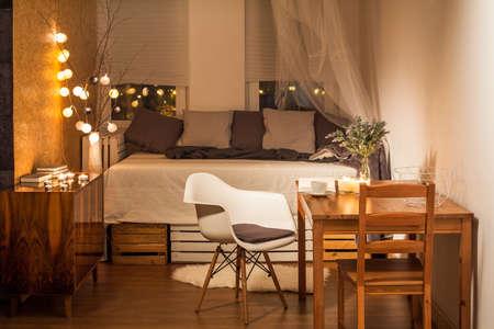 decoracion mesas: Habitación en marrón y beige con cama, silla y mesa