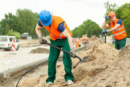obrero trabajando: trabajador de la construcción joven que trabaja difícilmente con la espada Foto de archivo