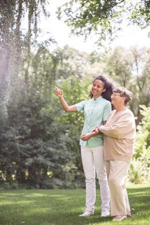 Jonge verpleegster is in gesprek met oudere vrouw Stockfoto