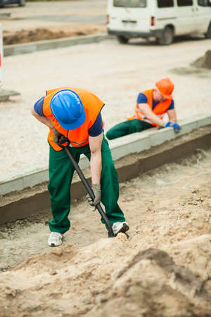 kerb: Two workers working hard at road construction Stock Photo