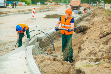 Jonge handarbeider het opgraven van een weg met behulp van spade Stockfoto