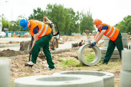 trundle: Young building workers during road construction work Stock Photo