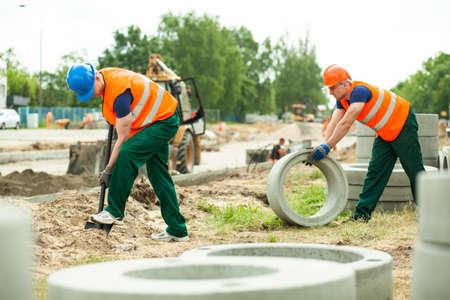 Jonge werknemers gebouw tijdens de wegenbouw werk