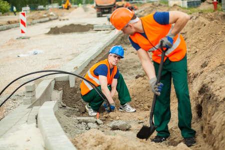 terreno: Operaio di costruzione l'installazione di cavi elettrici in cantiere