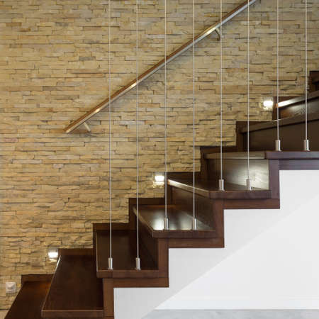 handrail: Wooden stairway and brick wall in luxury anteroom