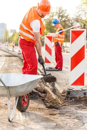 casco rojo: Imagen de fuertes trabajadores de la construcción en la plataforma de construcción Foto de archivo