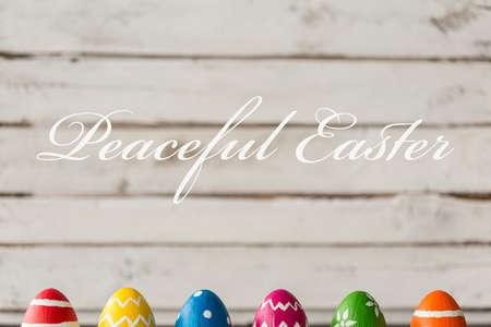 Tiro de huevos de Pascua en una fila y escritura 'Pascua pacífica'