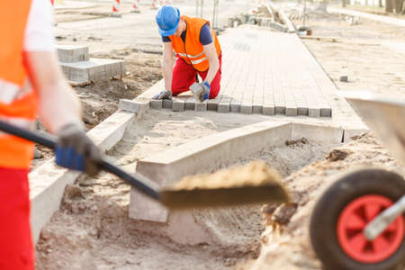 kerb: Photo of young construction worker laying new cobblestones